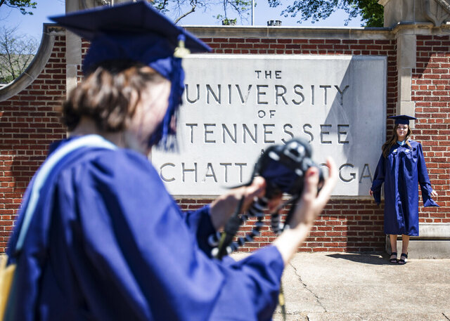 The University of Tennessee at Chattanooga graduate students Molly Felty, right, and Lauren Watkins take turns photographing themselves in their caps and gowns in front of the UTC sign on McCallie Avenue, Friday, May 1, 2020, in Chattanooga, Tenn. Spring 2020 Commencement ceremonies are postponed to August 7 and 8 due to the coronavirus pandemic. (Troy Stolt/Chattanooga Times Free Press via AP)