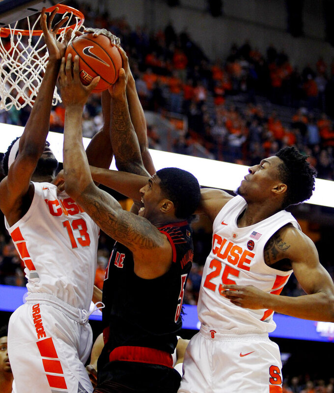 Syracuse's Paschal Chukwu, left, Louisville's Malik Williams, center, and Syracuse's Tyus Battle, right, battle for a rebound during the first half of an NCAA college basketball game in Syracuse, N.Y., Wednesday, Feb. 20, 2019. (AP Photo/Nick Lisi)