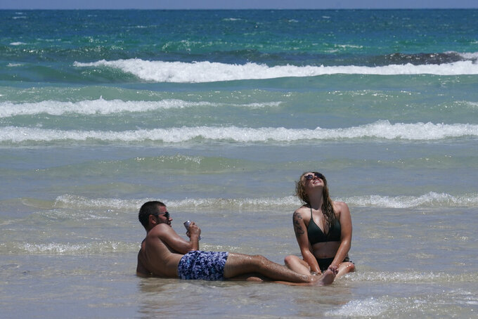 A couple enjoys the beach while sitting on a sandbar, Wednesday, May 26, 2021, in Miami Beach, Fla. The nation's tourist destinations are facing a severe worker shortage just as they try to rebound from a year lost to the coronavirus pandemic. (AP Photo/Marta Lavandier)