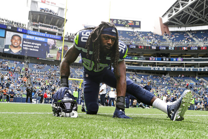 Seattle Seahawks defensive end Jadeveon Clowney stretches before an NFL football game against the Cincinnati Bengals, Sunday, Sept. 8, 2019, in Seattle. (AP Photo/John Froschauer)