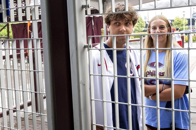 Fans stand outside a locked gate of Citizens Bank Park after the baseball game between the Philadelphia Phillies and Washington Nationals was suspended due to COVID-19 issues among the Nationals, Wednesday, July 28, 2021, in Philadelphia. (AP Photo/Laurence Kesterson)
