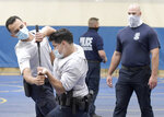 Baltimore city police trainee Antonio Martinez, second from left, of Philadelphia, defends his baton against trainee Maurice Rodriguez, left, of Pennington, N.J., as police instructor Robert Lance, right, watches during defense tactic training, Wednesday, Aug. 4, 2021, in Baltimore. (AP Photo/Steve Ruark)
