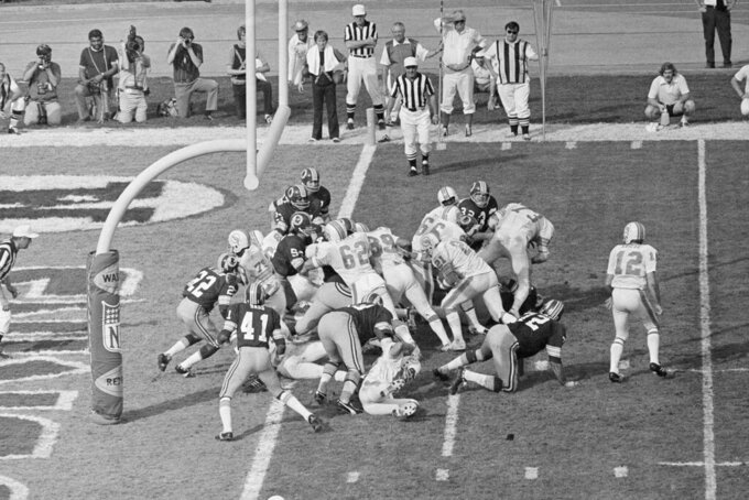 FILE - In this Jan. 14, 1973 file photo, Miami Dolphins' Jim Kiick (21) follows teammates Jim Langer (62) and Larry Csonka (39) to score against the Washington Redskins during Super Bowl VII in Los Angeles. The perfection of the 1972 Miami Dolphins has earned them the nod as the NFL's greatest team. The 1972 Dolphins edged the 1985 Chicago Bears for the NFL's greatest team in balloting by 59 national media members as part of the NFL's celebration of its 100th season. (AP Photo)
