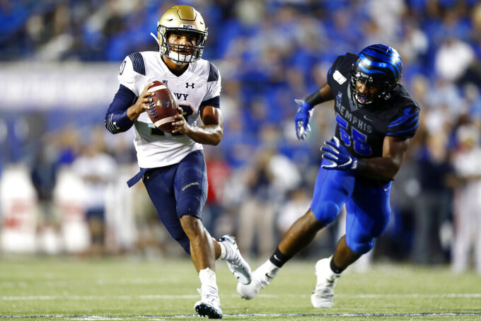 Navy quarterback Malcolm Perry, left, scrambles out of the pocket away from Memphis defensive end Bryce Huff during an NCAA college football game in Memphis, Tenn., Thursday, Sept. 26, 2019. (Joe Rondone/The Commercial Appeal via AP)