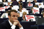 French President Emmanuel Macron listens to speeches at the European Parliament in Strasbourg, eastern France, Tuesday, April 17, 2018 as European lawmakers raise placards reading