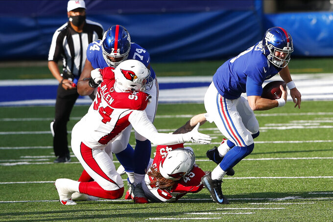 New York Giants quarterback Daniel Jones, right, is brought down by Arizona Cardinals defense during the first half of an NFL football game, Sunday, Dec. 13, 2020, in East Rutherford, N.J. (AP Photo/Noah K. Murray)