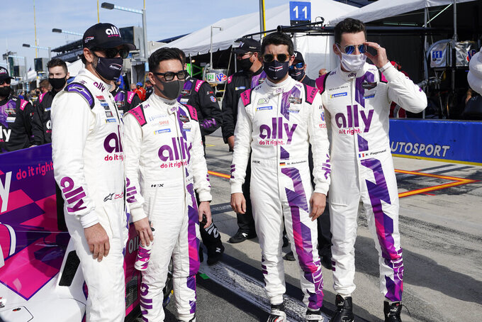 IMSA Series driving team from left, Jimmie Johnson, Kamui Kobayashi, Mike Rockenfeller and Simon Pagenaud gather for a photo before the start of the Rolex 24 hour auto race at Daytona International Speedway, Saturday, Jan. 30, 2021, in Daytona Beach, Fla. (AP Photo/John Raoux)