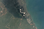 In this satellite photo released from Planet Labs Inc., a plume of smoke rising over the Pertamina Balongan Refinery in Indonesia's West Java province Monday, March 29, 2021. At least 500 people were being evacuated Monday from a nearby village after the massive fire broke out at the Pertamina Balongan Refinery in Indonesia's West Java province. (Planet Labs Inc. via AP)
