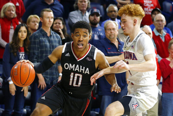 Omaha guard Ayo Akinwole (10) drives on Arizona guard Nico Mannion in the first half during an NCAA college basketball game, Wednesday, Dec. 11, 2019, in Tucson, Ariz. (AP Photo/Rick Scuteri)