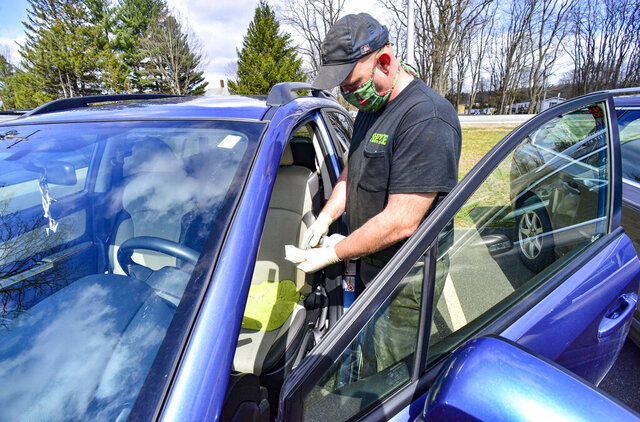 Mike Coombs, technician at Shippee Auto, in Hinsdale, N.H., disinfects each vehicle before and after doing repairs on them to help prevent the spread of coronavirus, Wednesday, April 22, 2020. (Kristopher Radder/The Brattleboro Reformer via AP)