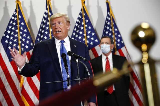 President Donald Trump speaks with reporters after meeting with Senate Republicans at their weekly luncheon on Capitol Hill in Washington, Tuesday, May 19, 2020. Standing behind Trump is Sen. John Barrasso, R-Wyo. (AP Photo/Patrick Semansky)