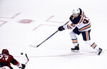 Edmonton Oilers center Ryan Nugent-Hopkins (93) sends the puck past Arizona Coyotes defenseman Alex Goligoski (33) for an empty-net goal during the third period of an NHL hockey game Friday, Jan. 12, 2018, in Glendale, Ariz. The Oilers defeated the Coyotes 4-2. (AP Photo/Ross D. Franklin)