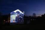 An image of veteran Chester LaPlante is projected onto the home of his son, Randy LaPlante, as he looks out a window with his wife, Nicole, and their sons, Evan and Blake, at their home in Amsterdam, N.Y., Tuesday, May 5, 2020. LaPlante, a U.S. Army veteran and resident of the Soldier's Home in Holyoke, Mass., died from the COVID-19 virus at the age of 78. Seeking to capture moments of private mourning at a time of global isolation, the photographer used a projector to cast large images of veterans on to the homes as their loved ones are struggling to honor them during a lockdown that has sidelined many funeral traditions. (AP Photo/David Goldman)