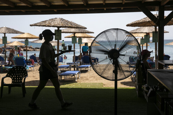 A waitress serves refreshments at a beach bar of Lagonissi village, a few miles southwest of Athens, on Thursday, July 29, 2021. One of the most severe heat waves recorded since 1980s scorched southeast Europe on Thursday, sending residents flocking to the coast, public fountains and air-conditioned locations to find some relief, with temperatures rose above 40 C (104 F) in parts of Greece and across much of the region. (AP Photo/Yorgos Karahalis)