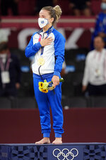 Gold medalist Distria Krasniqi of Kosovo reacts during the medal ceremony for women's -48kg judo at the 2020 Summer Olympics, Saturday, July 24, 2021, in Tokyo, Japan. (AP Photo/Vincent Thian)