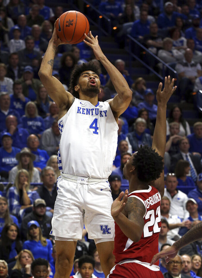 Kentucky's Nick Richards (4) shoots in front of Arkansas' Gabe Osabuohien (22) during the first half of an NCAA college basketball game in Lexington, Ky., Tuesday, Feb. 26, 2019. (AP Photo/James Crisp)