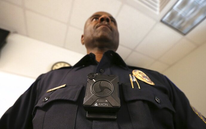 Phoenix Police Department Sgt. Kevin Johnson shows off the new Axon Body 2 body camera after demonstrating to fellow officers how the camera works as another precinct gets their cameras assigned to them Wednesday, July 3, 2019, in Phoenix.  Although body-worn cameras are becoming a police standard nationwide, Phoenix was among the last big departments to adopt their widespread use. (AP Photo/Ross D. Franklin)