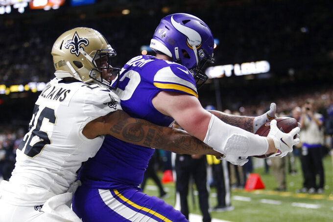 Minnesota Vikings tight end Kyle Rudolph pulls in the game winning touchdown pass over New Orleans Saints cornerback P.J. Williams (26) during overtime of an NFL wild-card playoff football game, Sunday, Jan. 5, 2020, in New Orleans. The Vikings won 26-20. (AP Photo/Brett Duke)
