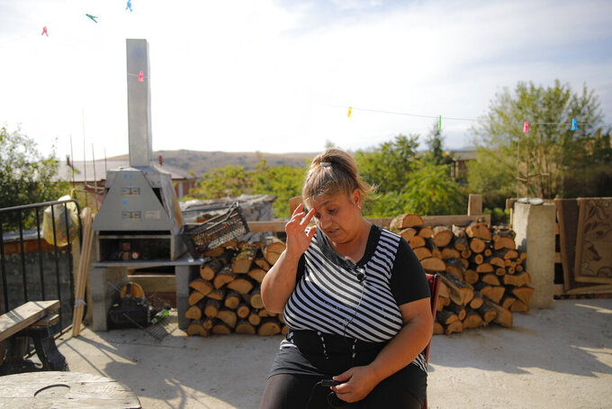 """Azime Ali Topchu, 48, a Bulgarian Roma woman, gestures during an interview with the Associated Press in a village on the outskirts of Burgas, Bulgaria, Monday, Sept. 28, 2020. Human rights activists and experts say local officials in several countries with significant Roma populations have used the pandemic to unlawfully target the minority group, which is Europe's largest and has faced centuries of severe discrimination. Topchu said that the police-enforced lockdown of her village in Burgas, on Bulgaria's Black Sea Coast, made her family """"really sad."""" (AP Photo/Vadim Ghirda)"""