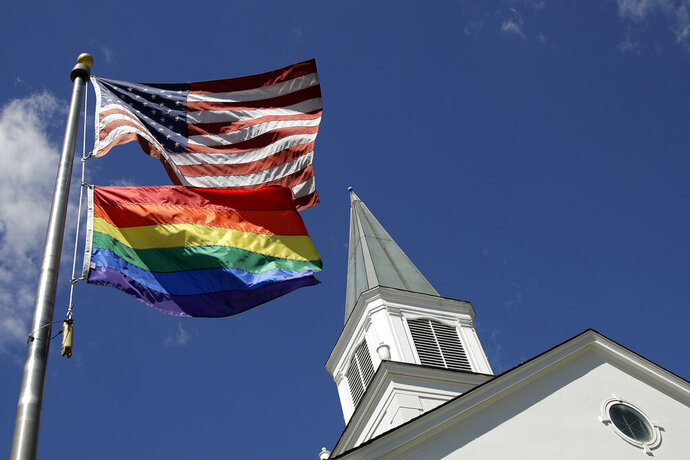 FILE - In this April 19, 2019, file photo, a gay pride rainbow flag flies along with the U.S. flag in front of the Asbury United Methodist Church in Prairie Village, Kan., United Methodist Church leaders are proposing creation of a separate division that would let more traditional denominations break away because of the disagreement with churches over the UMC's official stance on gay marriage. (AP Photo/Charlie Riedel, File)