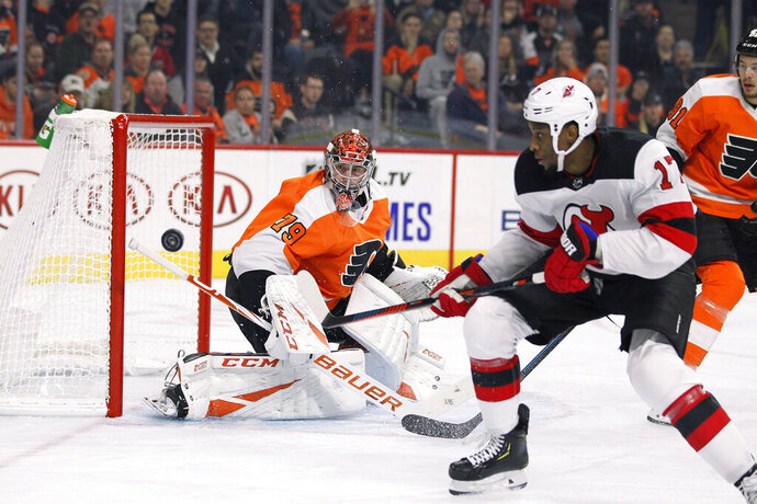 New Jersey Devils' Wayne Simmonds, right, chases the puck as Philadelphia Flyers' Carter Hartnwatches during the first period of an NHL hockey game Wednesday, Oct. 9, 2019, in Philadelphia. (AP Photo/Tom Mihalek)