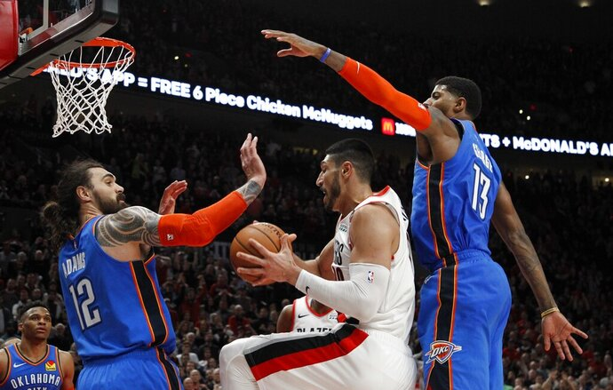 Portland Trail Blazers center Enes Kanter, center, grabs a rebound as Oklahoma City Thunder center Steven Adams, front left, and Thunder forward Paul George, right, defend during the second half of Game 1 of a first-round NBA basketball playoff series in Portland, Ore., Sunday, April 14, 2019. (AP Photo/Steve Dipaola)