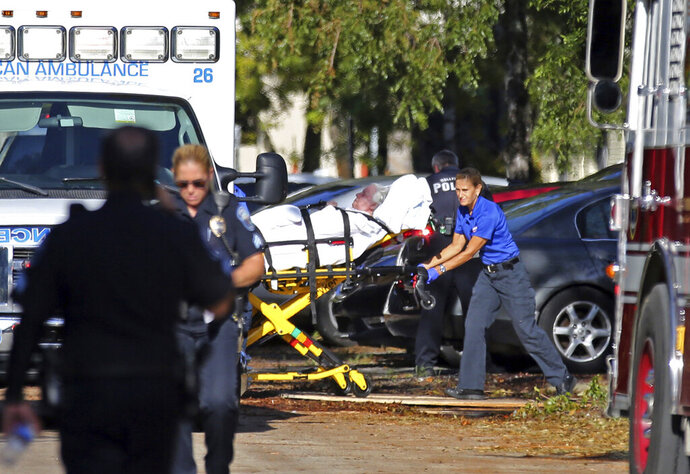 FILE - In this Wednesday, Sept. 13, 2017 file photo, a woman is transported from The Rehabilitation Center at Hollywood Hills as patients are evacuated after a loss of air conditioning due to Hurricane Irma in Hollywood, Fla. Defense attorneys said Sunday, August 25, 2019 that arrests are expected shortly in the case of a Florida nursing home where 12 elderly patients died after the complex lost power and was engulfed by sweltering heat during a powerful 2017 hurricane. (Amy Beth Bennett/South Florida Sun-Sentinel via AP, File)