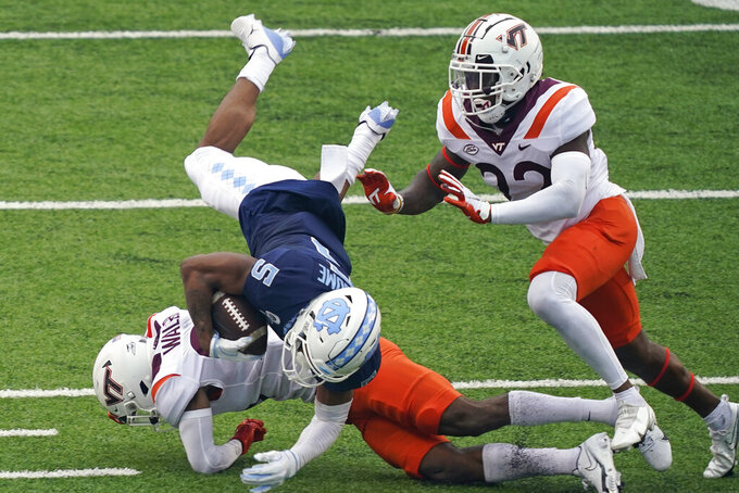 North Carolina wide receiver Dazz Newsome (5) is tackled by Virginia Tech defensive back Jermaine Waller as defensive back Chamarri Conner assists during the first half of an NCAA college football game in Chapel Hill, N.C., Saturday, Oct. 10, 2020. (AP Photo/Gerry Broome)