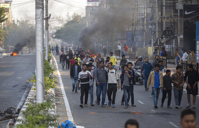 Protestors walk past burning tires defying curfew in Gauhati, India, Thursday, Dec. 12, 2019. Police arrested dozens of people and enforced curfew on Thursday in several districts in India's northeastern Assam state where thousands protested legislation granting citizenship to non-Muslims who migrated from neighboring countries. (AP Photo/Anupam Nath)