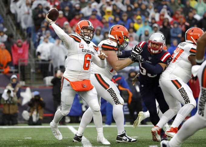 Cleveland Browns quarterback Baker Mayfield, left, passes against the New England Patriots in the first half of an NFL football game, Sunday, Oct. 27, 2019, in Foxborough, Mass. (AP Photo/Elise Amendola)