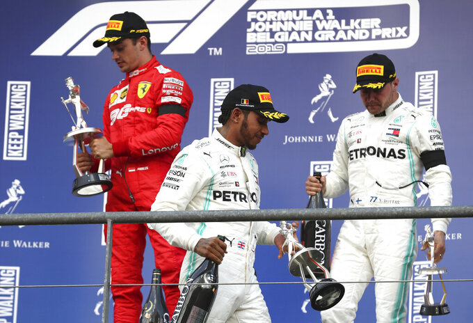 Ferrari driver Charles Leclerc of Monaco, left, holds his trophy on the podium after finishing first in the Belgian Formula One Grand Prix in Spa-Francorchamps, Belgium, Sunday, Sept. 1, 2019. Mercedes driver Lewis Hamilton of Britain. center, placed second and Mercedes driver Valtteri Bottas of Finland, right, placed third. (AP Photo/Francisco Seco)