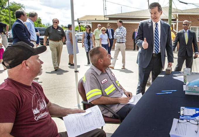 North Carolina Governor Roy Cooper gives a thumbs-up to Pine Hall Brick employees registering to receive a COVID-19 vaccine at the brick plant's clinic in Madison, N.C., on Thursday, May 27, 2021. (Woody Marshall/News & Record via AP)