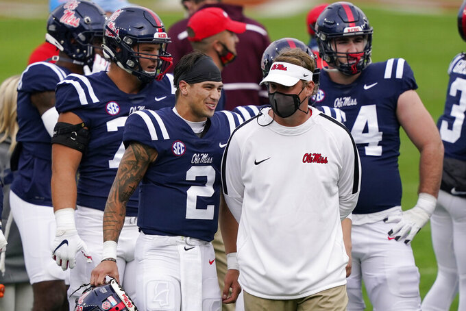 Mississippi quarterback Matt Corral (2) and coach Lane Kiffin talk before the team's NCAA college football game against Mississippi State, Saturday, Nov. 28, 2020, in Oxford, Miss. Mississippi won 31-24. (AP Photo/Rogelio V. Solis)