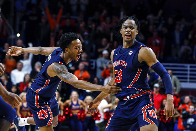 Auburn forward Isaac Okoro (23) celebrates with Auburn guard Jamal Johnson (1) after defeating South Alabama during the second half of an NCAA college basketball game, Tuesday, Nov. 12, 2019, in Mobile, Ala. Auburn won 70-69. (AP Photo/Butch Dill)