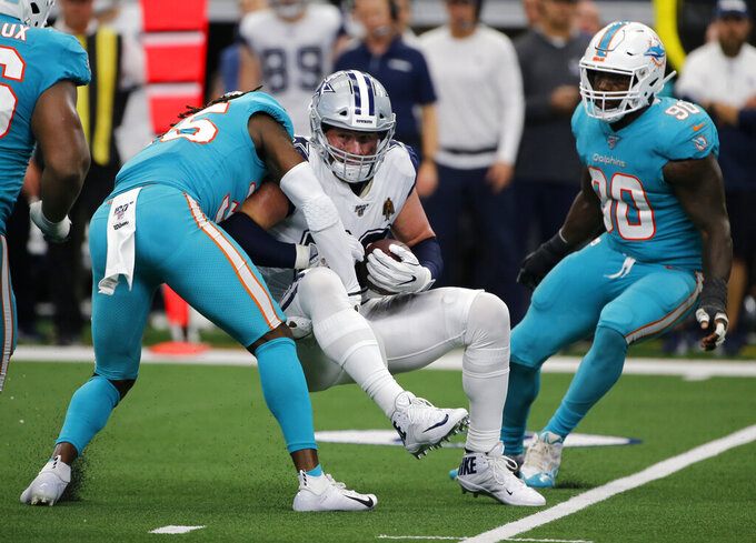 Miami Dolphins defensive back Walt Aikens (35) and Charles Harris (90) combine to stop Dallas Cowboys tight end Jason Witten (82) from advancing after catching a pass in the second half of an NFL football game in Arlington, Texas, Sunday, Sept. 22, 2019. (AP Photo/Michael Ainsworth)