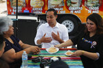 FILE - In this Feb. 28, 2019 file photo former Housing and Urban Development Secretary and Democratic presidential candidate Julian Castro speaks with Lupe Arreola, left, Astrid Silva, right, and others while visiting a taco truck, in North Las Vegas, Nev. As Democrats jockey for support in Nevada, a meeting with Silva, a 31-year-old immigrant rights activist who has become a public face of the
