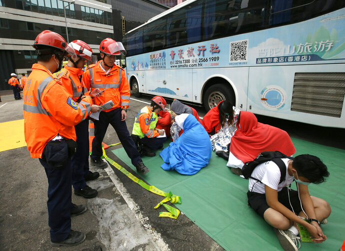 Medical workers take care of protesters near the Hong Kong Polytechnic University in Hong Kong, Tuesday, Nov. 19, 2019. About 100 anti-government protesters remained holed up at the Hong Kong university Tuesday, unsure what to do next as food supplies dwindled and a police siege of the campus entered its third day. (AP Photo/Achmad Ibrahim)