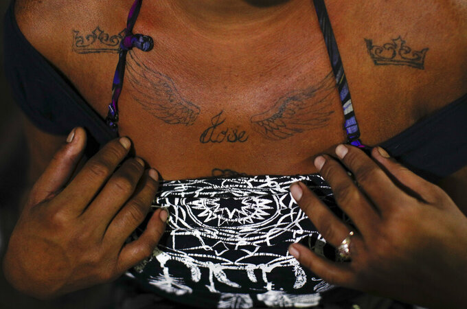 A 27-year-old transgender sex worker who goes by the name Angora shows the tattoo she had done to remember her 14-year-old brother Jose, who was murdered back home in Honduras after becoming an assistant to a group of horse thieves, as she waits for clients outside the Revolution subway station in Mexico City, Tuesday, March 9, 2021. Angora says the competition for clients since the cornavirus pandemic began has exacerbated discrimination against immigrant sex workers from Central America in Mexico City. (AP Photo/Rebecca Blackwell)