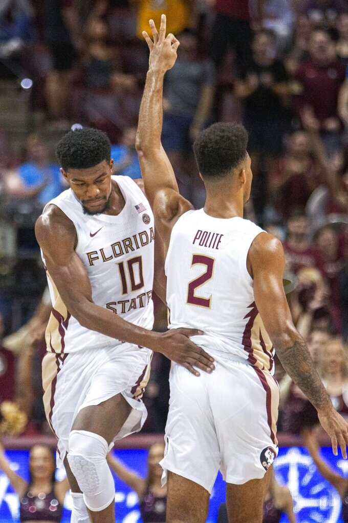 Florida State forward Malik Osborne (10) congratulates guard Anthony Polite (2) after a 3-point shot during the first half of the team's NCAA college basketball game against Virginia in Tallahassee, Fla., Wednesday, Jan. 15, 2020. (AP Photo/Mark Wallheiser)
