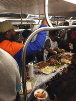 """This Sunday, Nov. 24, 2019, photo provided by Wake Coulter shows a Thanksgiving meal being served on a New York City subway L Train. Stand-up comedian Jodell """"Joe Show"""" Lewis tells the New York Post he organized the Thanksgiving dinner to """"bring a little excitement to commuters"""" and feed any New Yorkers who might be hungry.  (Wake Coulter via AP)"""