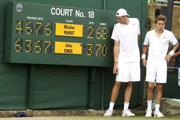 FILE - In this June 24, 2010, file photo, John Isner of the United States, left, and France's Nicolas Mahut pose for a photo next to the scoreboard following their epic men's singles match at the All England Lawn Tennis Championships at Wimbledon. The Australian Open and Wimbledon are finally doing what the U.S. Open has done for decades: figuring out a way to end a fifth set before it becomes another 26-24 slog or _ perish the thought _ 70-68. While some fans and others might still like the idea that a match could go on and on and on forever, or seemingly forever, players such as John Isner are thrilled about the change. (AP Photo/Alastair Grant, Pool, File)