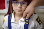 Dani Nelson, 7, wears a junior fire badge covered in black tape, a gesture of mourning, by her father, Chris Nelson, a member of the Enfield Volunteer Fire Company where Sgt. James Johnston once served, before a memorial procession for him in Enfield, N.Y., Saturday, Aug. 31, 2019. Johnston, an explosive ordnance disposal specialist, had been killed along with a Green Beret on June 25 in Uruzgan Province in south-central Afghanistan. (AP Photo/David Goldman)