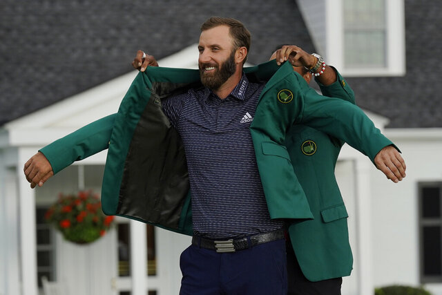 Tiger Woods helps Masters champion Dustin Johnson with his green jacket after his victory at the Masters golf tournament Sunday, Nov. 15, 2020, in Augusta, Ga. (AP Photo/David J. Phillip)