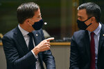 Dutch Prime Minister Mark Rutte, left, speaks with Spain's Prime Minister Pedro Sanchez during a round table meeting at an EU summit in Brussels, Monday, July 20, 2020. Weary European Union leaders are expressing cautious optimism that a deal is in sight on their fourth day of wrangling over an unprecedented budget and coronavirus recovery fund. (John Thys, Pool Photo via AP)