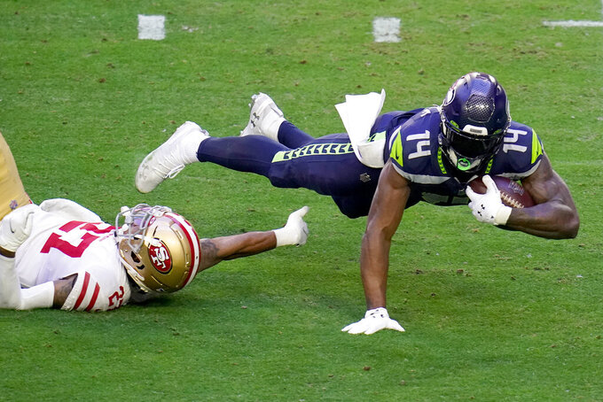 CORRECTS TO 49ERS CORNERBACK DONTAE JOHNSON NOT 49ERS CORNERBACK JASON VERRETT - Seattle Seahawks wide receiver DK Metcalf (14) is tackled after a catch by San Francisco 49ers cornerback Dontae Johnson, left, during the first half of an NFL football game, Sunday, Jan. 3, 2021, in Glendale, Ariz. With the catch, Metcalf passed former Seahawk Steve Largent's single-season franchise record of 1,287 receiving yards set in 1985. (AP Photo/Ross D. Franklin)