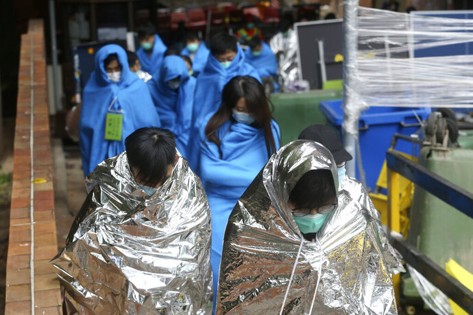Injured protesters huddle under blankets as they walk at the Hong Kong Polytechnic University in Hong Kong, Tuesday, Nov. 19, 2019. About 100 anti-government protesters remained holed up at a Hong Kong university Tuesday as a police siege of the campus entered its third day. (AP Photo/Achmad Ibrahim)