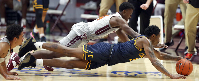 Virginia Tech's Nahiem Alleyne, top, and Coppin State's Koby Thomas dive for a loose ball during the first half of an NCAA college basketball game, Saturday, Dec. 19, 2020 in Blacksburg, Va. (Matt Gentry/The Roanoke Times via AP, Pool)