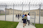 FILE – This June 1, 2018, file photo, shows a tour group entering block D in the west section of the State Correctional Institution at Phoenix in Collegeville, Pa. The first phase of transferring more than 2,500 inmates from the 89-year-old state prison at Graterford to the long-delayed $400 million SCI Phoenix prison began Wednesday, July 11, 2018, according to the Pennsylvania Department of Corrections, which plans to bus hundreds of inmates a day to the new prison facility about a mile down the road until all are relocated. (AP Photo/Jacqueline Larma, File)