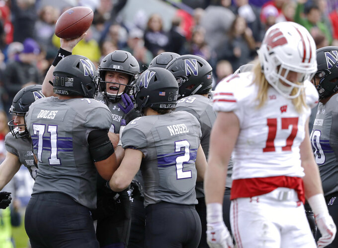 Northwestern quarterback Clayton Thorson (18) celebrates with teammates after scoring a touchdown as Wisconsin linebacker Andrew Van Ginkel (17) looks down at the ground during the first half of an NCAA college football game in Evanston, Ill., Saturday, Oct. 27, 2018. (AP Photo/Nam Y. Huh)