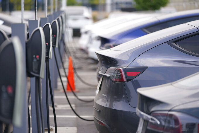 """This Aug. 23, 2020 photo shows a long line of unsold 2020 models charge outside a Tesla dealership in Littleton, Colo.  The European Union is lacking sufficient charging infrastructure for electric vehicles, according to the bloc's external auditor. In a report published Tuesday, April 13, 2021, the European Court of Auditors said users are gaining more harmonized access to charging networks but the EU is still """"a long way from reaching its Green Deal target of 1 million charging points by 2025."""" (AP Photo/David Zalubowski)"""